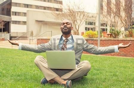 relax: Jeune homme d'affaires avec un ordinateur détente à l'extérieur siège social assis sur l'herbe verte en mode de médiation