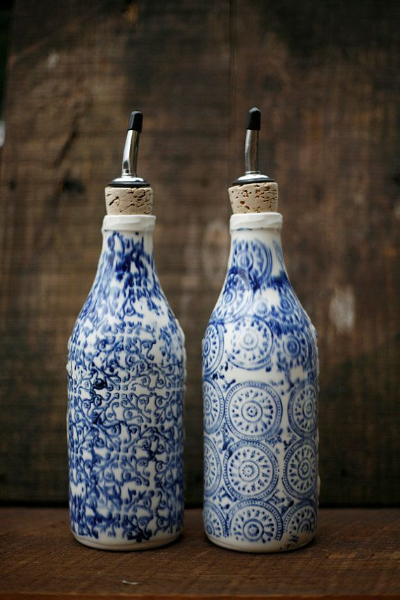 Oil and vinegar. But at $165… my idea is to paint two wine bottles white in a heat-tolerant paint, draw similar designs with a blue sharpie, bake them on (150 degrees for 30 minutes), pop in some tops like these, and tada! Done.