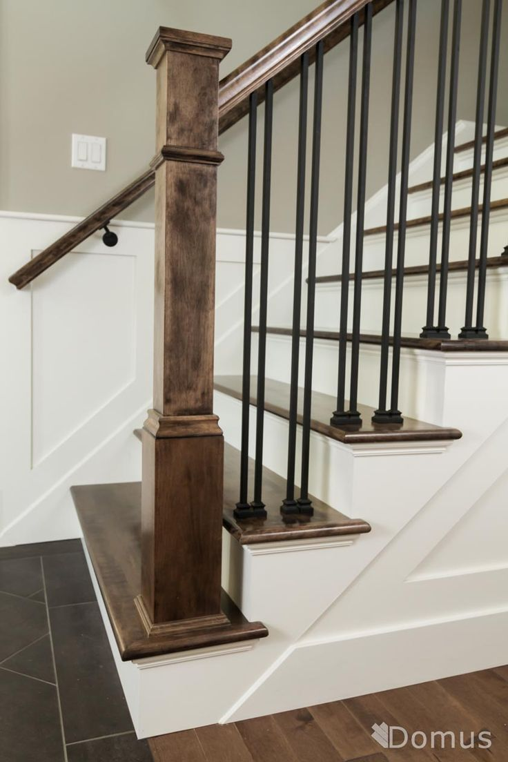 Staircase with white accents and black metal spindles and shoes More