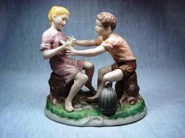 Conjunto escultório Biscuit em porcelana representando crianças brincando com pássaro.