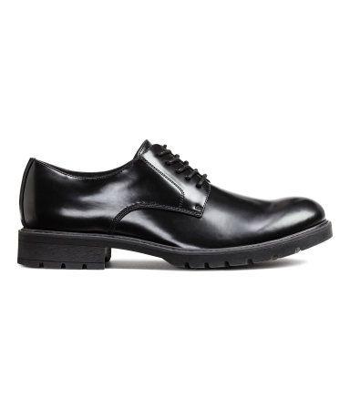 Zwart. Derbyschoenen van glanzend imitatieleer met een vetersluiting voor. De schoenen hebben een voering en een binnenzool van katoenen canvas en een