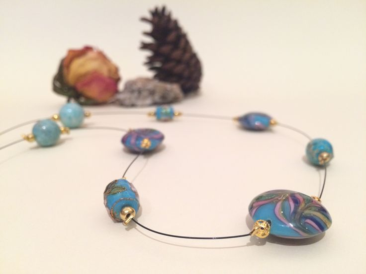 Blue shade glass beads enhanced by gold filigree, mounted on black wire