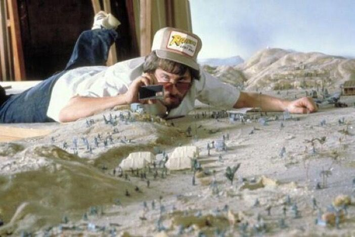 """Steven Spielberg examining a scale model on the set of """"Indiana Jones: Raiders of the Lost Ark"""", 1980."""