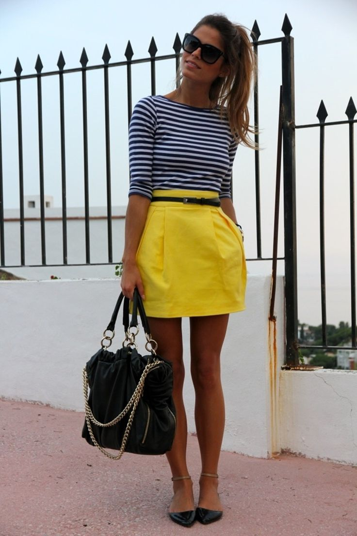 Outfit de oficina. Chica usando una falda amarilla, blusa de rayas y flats