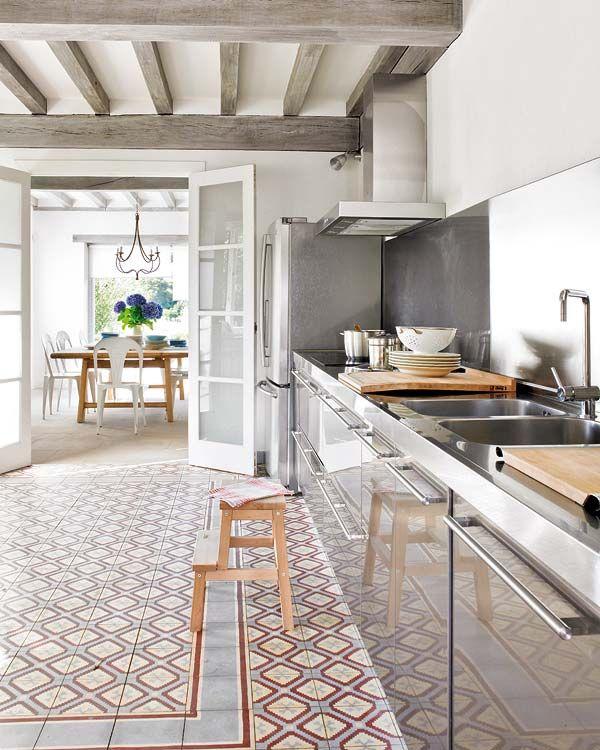 Cuisine tout inox - les carreaux de ciment en couleur au sol et les accessoires en bois réchauffent bien la pièce.