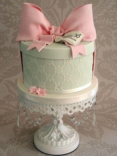 Um dos maiores exemplos de bolo clássico, fica lindo em qualquer ocasião ( um chá de bebê, aniversário de 1 ano ou até de 30 anos!). Veja a simplicidade: um bolo em forma de caixa rendada e um grande laço para arrematar! Apesar de simples visualmente, de execução muito delicada.
