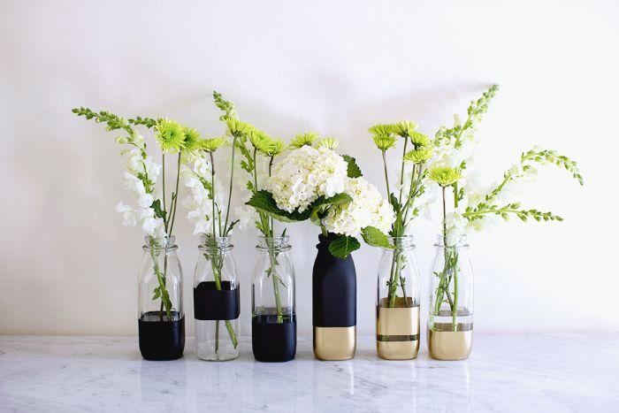 On a besoin de quoi ? - 6 bouteilles en verre vides - 1 spray de peinture effet tableau de classe ou noire - 1 spray de peinture dorée - des ciseaux - du gros scotch - un carton vide - des sacs pla...