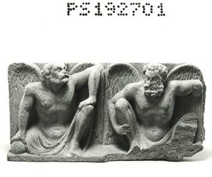 Panel with two atlantes. The atlas on the right recalls BM 1880.179, the other BM 1880.180; the wings of both curve smoothly at the top with rounded edges in relief, the coverts reach down to shoulder level, while the flight feathers end in one or more points. The arms show some indication of biceps. The gaunt figure on the left rests his hands on his knees and the