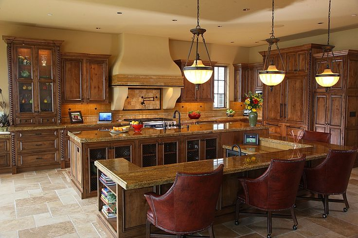 Large open kitchen is thoroughly dominated by multi-part island with full height counter space attached to C-shaped lower dining extension, replete with glass panel cabinetry and bookshelf space under rich marble countertops.