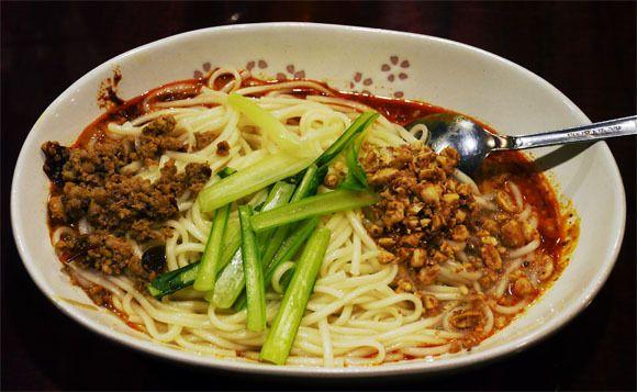 ドラマ『孤独のグルメ』主演・松重豊さんが「ウマすぎて個人的に再度行ってしまった店」に行ってみた / 中華料理 楊 汁なし担々麺 見た目はアッサリ系に思えるがとんでもない。よくかき混ぜて食べると「天下一品のこってりスープかよッ!」と思うほど超コッテリなのである。いや、これは『天下一品』以上のコッテリさである。その秘密はゴマダレとナッツにあった。どちらもマッタリ系のコッテリ食材なので、すごくコッテリなのに味の濃さで飽きることがないのである。  調味料や香辛料によって味を濃くしている店もあるが、そういう料理は「鋭い味の濃さ」になってしまう。しかし、ここの担々麺はゴマダレとナッツが本来が持っている「味の濃さ」を利用してコッテリ感を出しているため、非常に優しい味なのである。しかし、スパイシーなので辛すぎるのが苦手な人は要注意。だが、ほどよい辛さがとても心地よく感じた。これも松重さんが食べた料理で非常に美味しい。