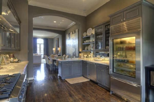 Love the Calcutta gold marble counters. calcutta gold marble countertops, gray peninsula, gray kitchen cabinets, chunky gray floating shelves, glass-front cabinets, white roman shade with gray ribbon trim, and glossy wood floors.    Sherwin Williams Porpoise
