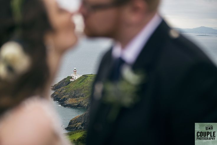 The bride & groom with the lighthouse between them. Wedding in The Abbey Tavern, Howth. Photographed by Couple Photography.