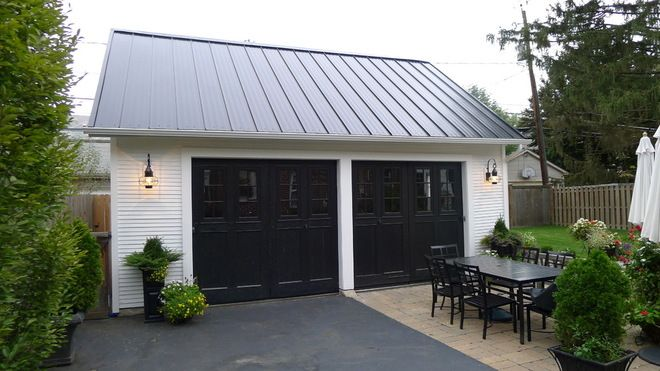 white detached garage with charcoal doors, metal roof....crushed dark granite driveway....use lights to match house
