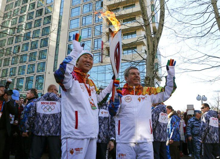 Presiden Komite Olimpiade Internasional Thomas Bach (kanan) memberikan obor Olimpiade pada Sekretaris Jenderal PBB Ban Ki-moon di SOchi (6/2). (AP/Shamil Zhumatov)