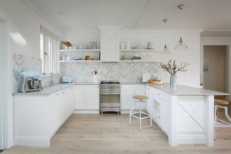 U shaped kitchen features white shaker cabinets paired with light gray quartz countertops, Caesarstone Clamshell Quartz, and a marble herringbone backsplash.