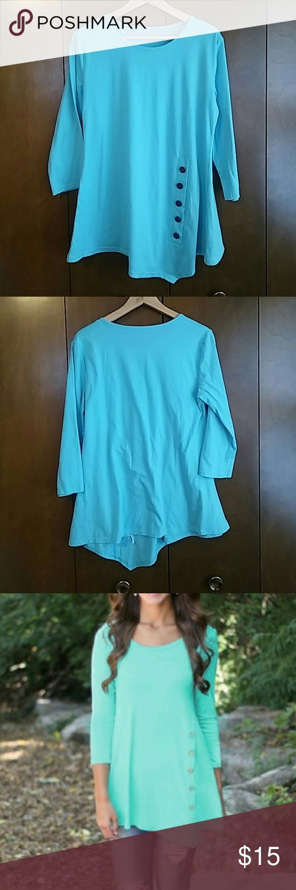 Shirt Asymmetrical Light blue/teal shirt with 3/4 length sleeves and brown buttons. The picture of it on the hangers are more true to the real color. NWOT. I bought it on line and it does not fit. I can not return it. It is an xl but fits more like a med-large. Tops Blouses