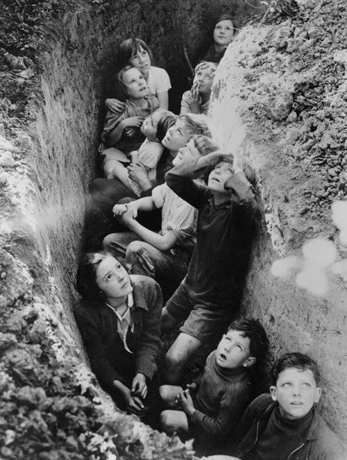 Children huddled in a bomb shelter experiencing an air raid during World War II, Britain, 1940