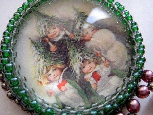 ガラスのカボションの中にヴィンテージカードの絵柄を閉じ込めました。 モミの木の妖精たちが描かれています。 ビーズで刺繍したブローチです。 揺れる小さなベルがポ...|ハンドメイド、手作り、手仕事品の通販・販売・購入ならCreema。