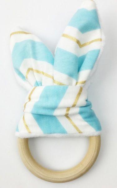 De bijtring, met bleu/ gold konijnenoren, is lekker om op te sabbelen, mee te knuffelen en leuk om mee te spelen. Ideaal voor baby's met doorkomende tandjes. Aan de ene kant een mooi katoenen stofje en aan de andere kant heerlijk zacht wit fleece met 'knispers' erin. De houten ring is gemaakt van onbewerkt hout, veilig voor baby's.  De doorsnede van de ring is 7 cm.  Ook erg leuk als Kraamcadeau