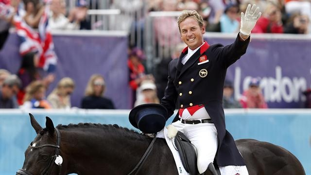 Britain's Carl Hester riding Uthopia waves after competing in the equestrian dressage individual grand prix special at the London 2012 Olympic Games in Greenwich Park August 7, 2012
