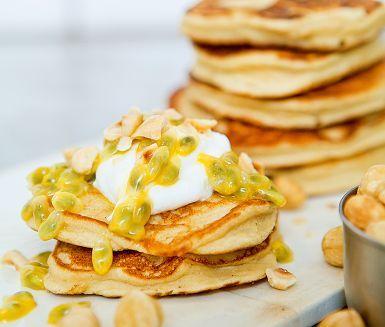 Bönpannkakor - en spännande variant på amerikanska pannkakor. Lika fluffiga, men betydligt nyttigare med kokta stora vita bönor och mandelmjöl som ingredienser. Servera bönpannkakorna direkt från stekpannan och toppa med kvarg, passionsfrukt och knapriga hasselnötter!