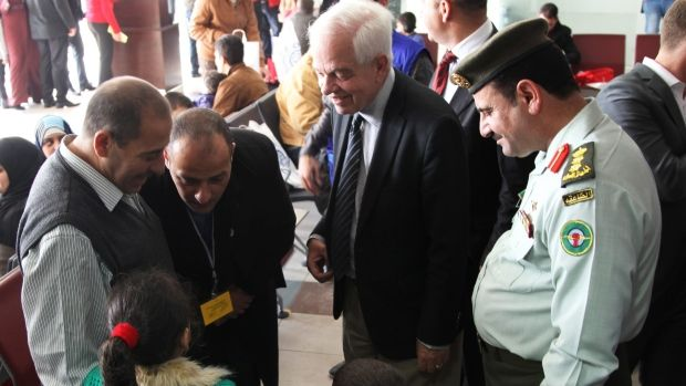 Canadian Minister of Immigration John McCallum, centre, talks with a Syrian family waiting to be flown to Canada late last year. New data finds that government-assisted refugees have higher than expected needs, with more children, lower language skills and lower education levels than those settled privately.