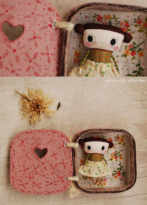 This is a small fabric doll painted by hand. Her hair is dark brown color. She comes in a handmade box. The lid is made to look like a door. The inside