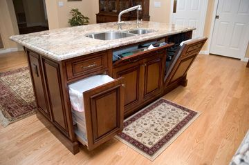 A compact island in a Phoenix Biltmore area kitchen remodel provides houses all of the essentials. Seating is located on back side, wainscot side panels have outlets. Working side features pull out trash and recycling, tilt-out drawer is located under sink and paneled dishwasher