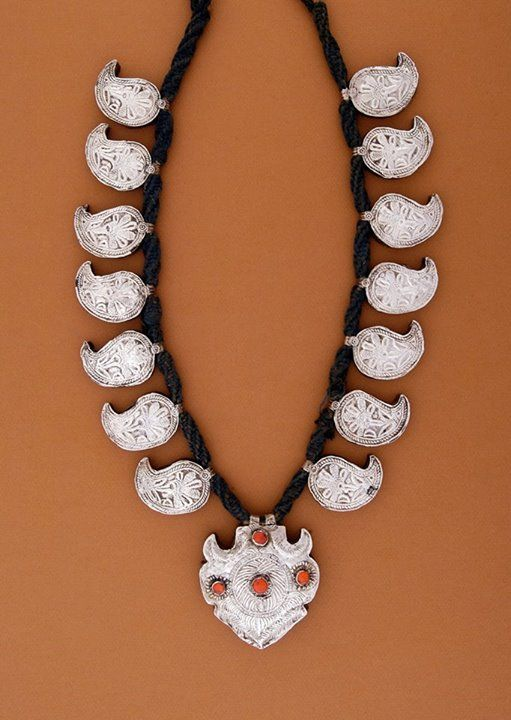 "Nepal, region north of Kathmandu| Necklace worn by the Tamang women; mango-shaped (""paisley"", ""boteh"") elements and an arrow-shaped central pendant made of silver, all attached to a thick cord (""dori""). The beads are coral or red glass.  