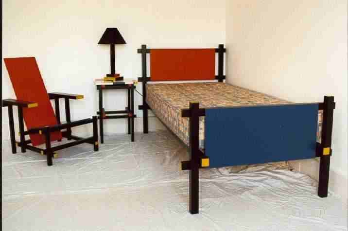 de stijl furniture, red and blue chair, bed, and side table
