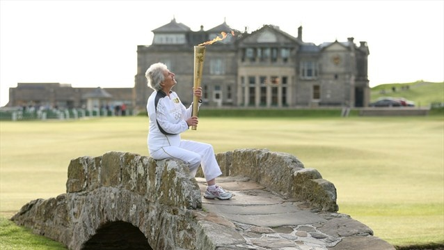Torchbearer Louise Martin holds the Olympic Flame whilst sitting on the Swilcan Bridge at St Andrews golf course during Day 26 of the London 2012 Olympic Torch Relay.