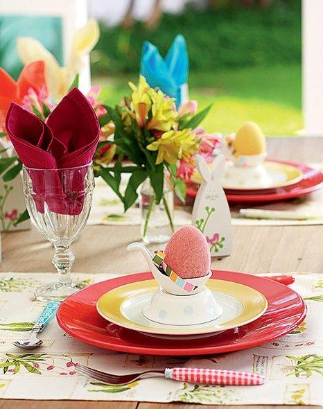 Outra ideia para a composição, que pode trazer uma mistura de louças coloridas. Os pratos rasos são vermelhos, os de sobremesa, amarelos, as colheres e os potinhos de porcelana, brancos. Nos copos, coloque os guardanapos em formato de orelha de coelho