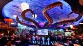 A giant octopus sits atop an aquarium where diners sit at a counter T-Rex at Downtown Disney