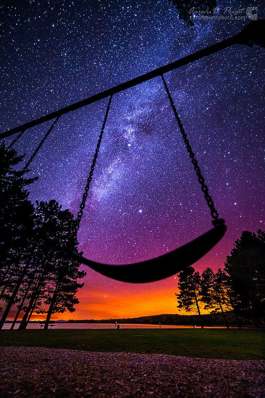 The Milky Way shines over a swing at Lily Bay State Park on Moosehead Lake, Maine, USA