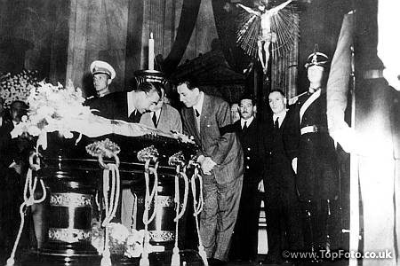 Death of Eva Peron President Juan Peron (wearing black armband) and rector P Camora , President of the Lower Chamber in the Parliament . look at the remains of Eva Peron after the body had been brought on a gun carriage from the Labour Ministry to Congress .  Juan Duarte , Eva's brother is standing beside the uniformed soldier. 13th August 1952