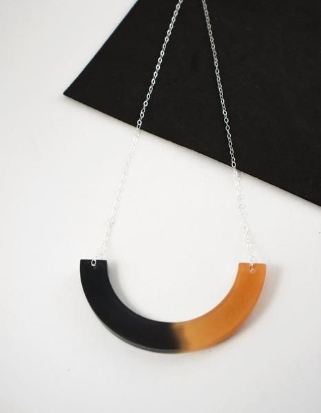 Unique and eye catching crescent pendant.  This black and bronze toned pendant has been handmade from resin, sterling silver wire and sterling silver chain.  A striking necklace in a modern and elegant design. It has been handmade by casting three seperate layers of black, bronze and clear resin. This has then been hand sanded and polished to give a lovely smooth appearance and feel. The necklace is completed with a sterling silver chain.