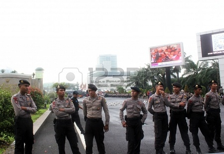 Police escort the demonstration of workers to protest the government's plan to raise the price of fuel, in front of the parliament building, Jakarta, on Monday, June 17, 2013.