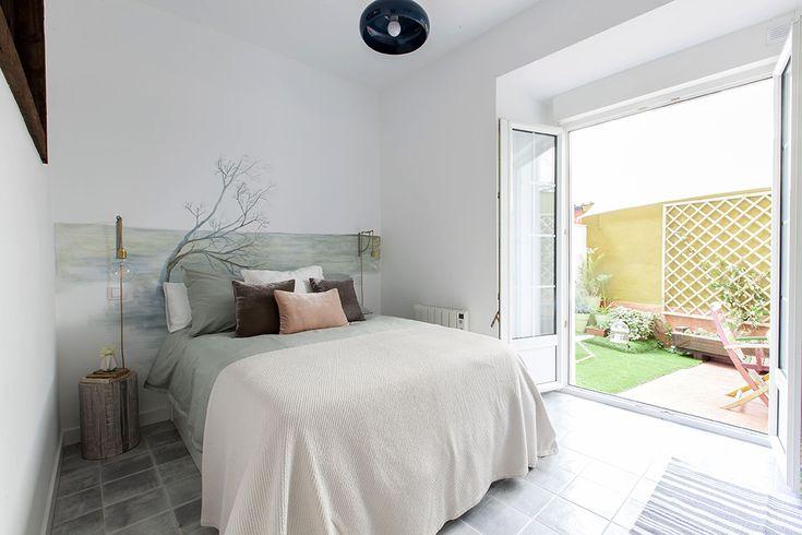 Dormitorio de matrimonio con salida a terraza. Destaca la mesilla que es un tronco de madera precioso en tonalidades grises.