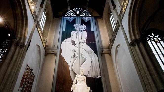 Het beeld van Monroe met mannen aan haar voeten springt als eerste inhet oog als je de Nieuwe Kerk betreedt