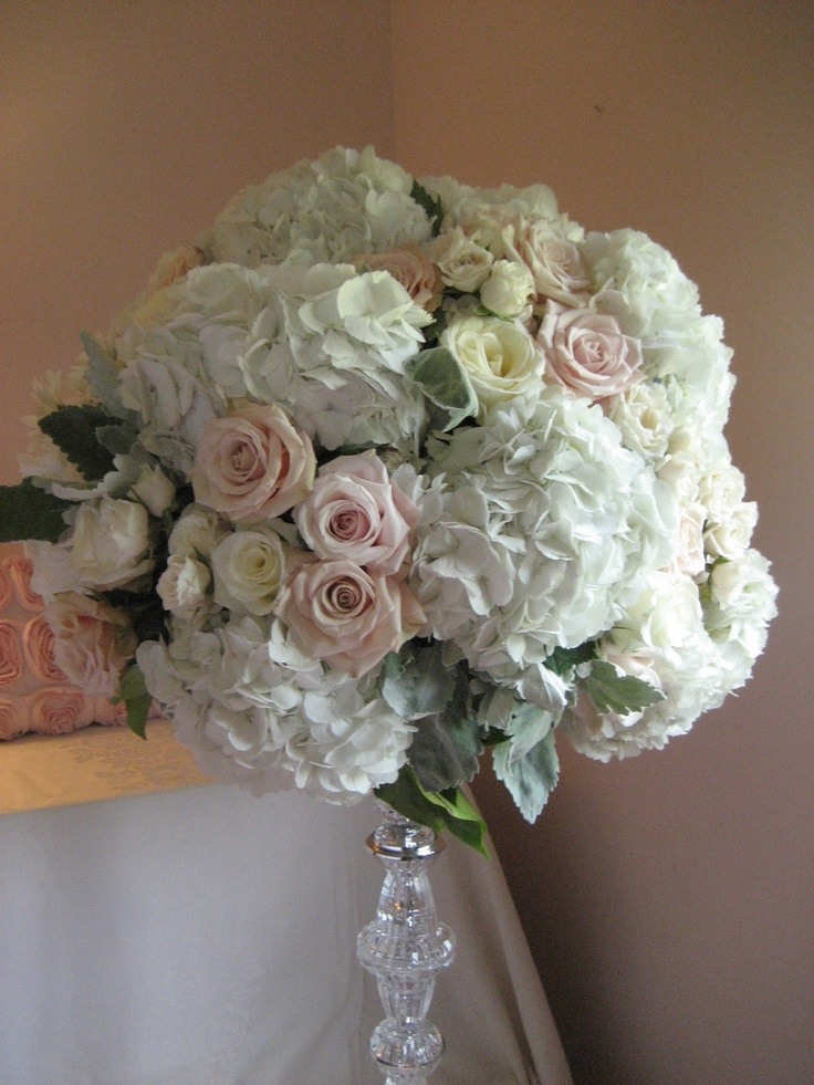 A lush arrangement of roses, hydrangea, and dusty miller  atop a cut crystal pedestal