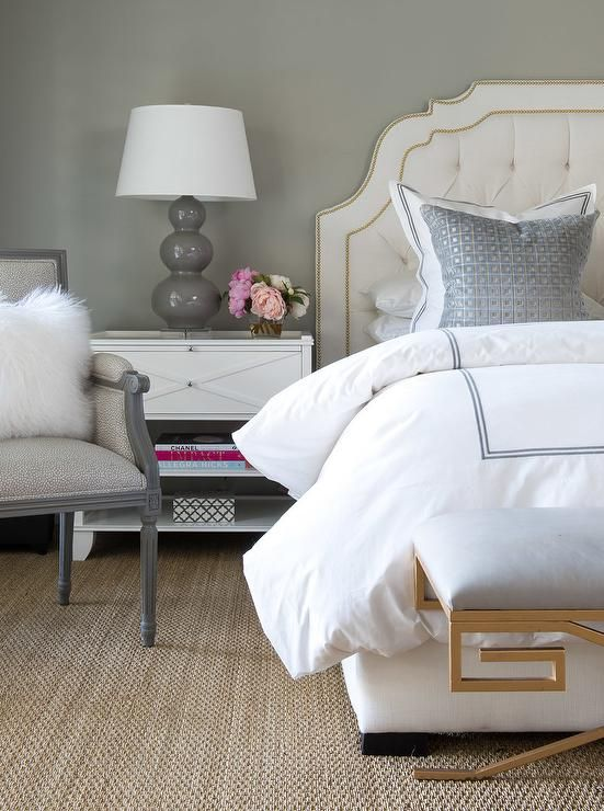 Tufted linen headboard with brass nailheads. Gray lamp on a white nightstand.