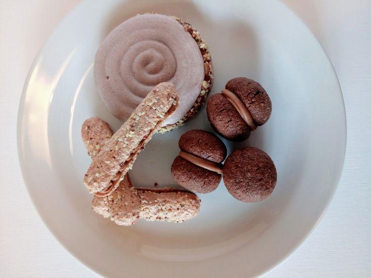 Biscotti a base di meringa, con ripieno di cremino alla nocciola. Baci di dama al cioccolato, friburghesi alle nocciole e meringhe al cacao.
