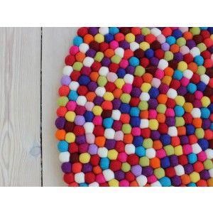 Den vackra och varma filtbollsmattan Dark Red tillhör en av våra nyaste designes.  Filtbollsmattans bas består av varma röda och lila nyanser, med en twist av friska blå och gröna färger. Filtbollsmattan kan användas på många ställen, där den kommer att skapa liv och värme. Det är en allround matta som kan användas överallt i huset eller på kontoret, men den är också populär i flickrummet.