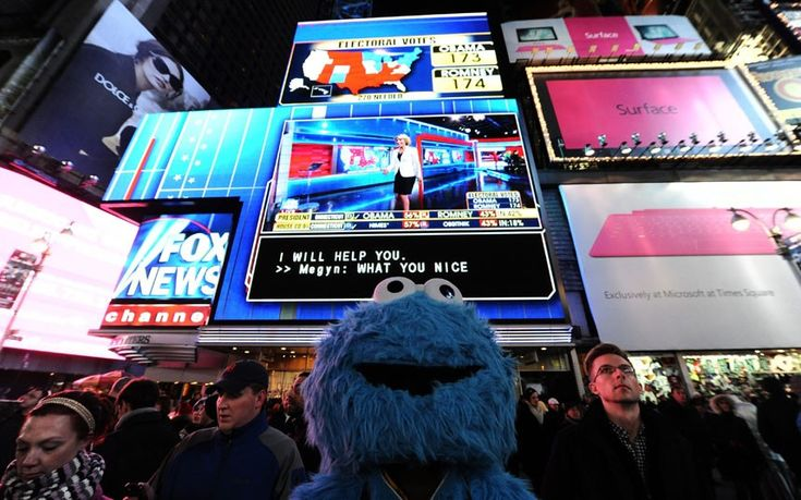 A man dressed as Cookie Monster watches large screens in Times Square as projected results in the 2012 US presidential election are broadcast in New York