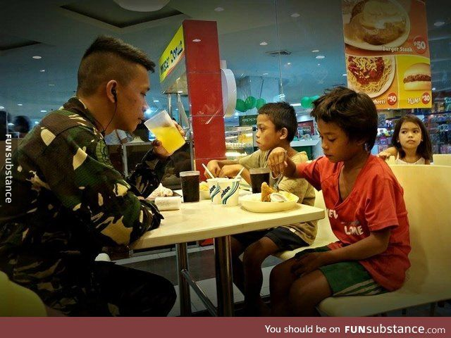 Philippine Air Force man buying meals for two street children