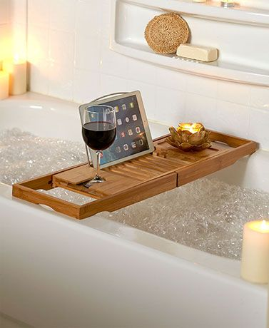 This Bamboo Bathtub Tray holds everything you need for a luxurious bath. It has an indented coaster slot for a wine glass, a built-in book/tablet rest and candle holder area