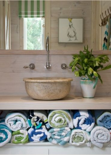 love the nautical stripe beach towels with pops of colour in a coastal bathroom