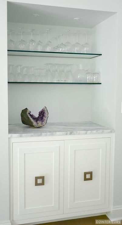 Chic bar nook is filled with stacked glass shelves over white cabinets adorned with brass square ...