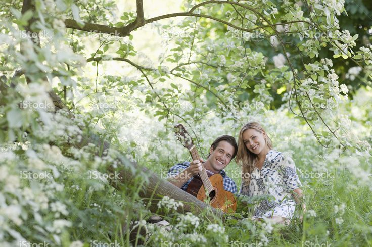 Man playing guitar for girlfriend in forest