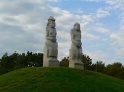 """Ópusztaszeri Nemzeti Történeti Emlékpark  A Nemzeti Emlékpark központi területén elhelyezett """"Őseink"""" kun szoborpár az 1239-ben Magyarországra betelepülő kunságnak állít emléket. A Radnai-hágó felé tekintő, halomra helyezett szobrok a Kis- és a Nagykunság településeinek földjeiből áll, amely a kun-magyar identitást, megmaradást, összefogást, összetartozást fejezi ki."""